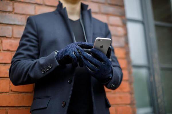 mężczyzna trzymający smartphone'a w rękawiczkach