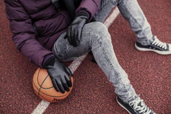 Mężczyzna w rękawiczkach skózanych siedzący na boisku opiera się o piłkę do koszykówki.