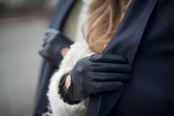 Elegancka kobieta w czarnych skórzanych rękawiczkach i granatowym płaszczu.