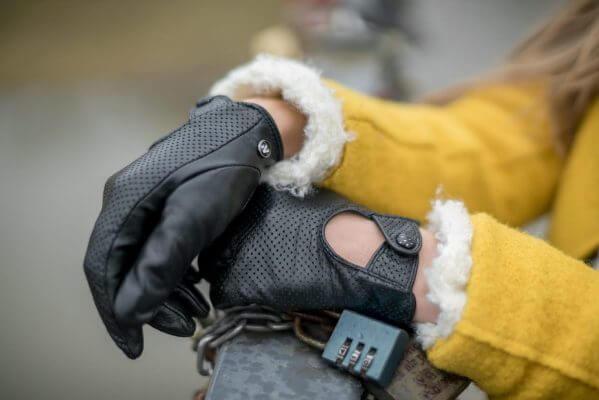 Kobieta w żółtym płaszczy i czarnych rękawiczkach opierająca się o barierkę.