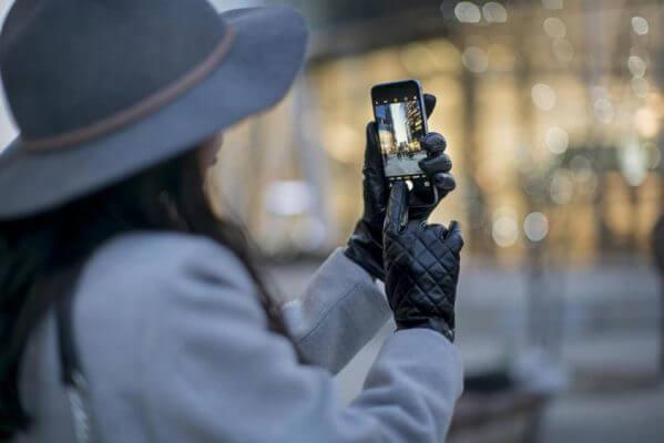 Kobieta obsługująca smartfon za pomocą skórzanych rękawiczek z obsługą ekranów dotykowych